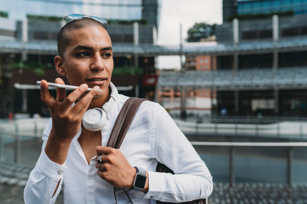 Young adult businessman sending a voicemail with smartphone in the city Young adult businessman sending a voicemail with smartphone in the city conference phone stock pictures, royalty-free photos & images