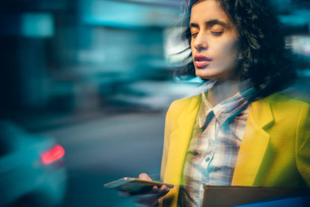Young adult businesswoman after heavy use of smartphone feels dizzy at night on a busy road. stock photo