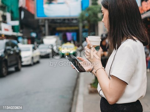 istock Young adult businesswoman looking for a taxi with a mobile phone 1134020924