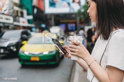 965004050 istock photo Young adult businesswoman looking for a taxi with a mobile phone 1197475400