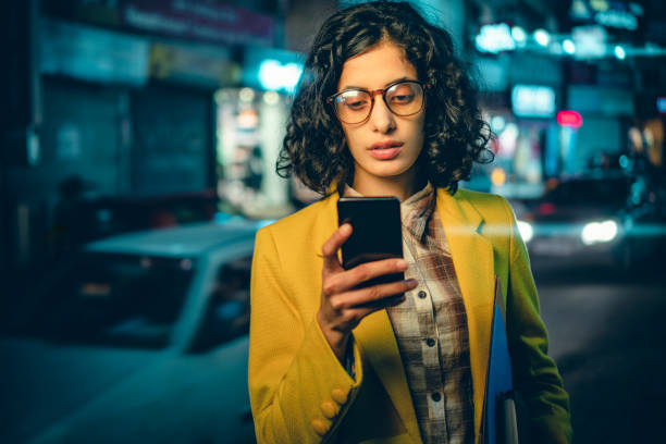 Young adult businesswoman reads a smartphone on a busy road at night. stock photo