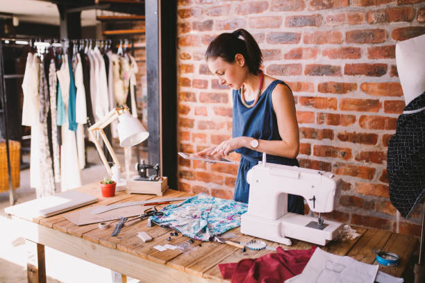 Young adult businesswoman working with digital tablet Young adult businesswoman working with digital tablet in fashion studio fashion designer stock pictures, royalty-free photos & images