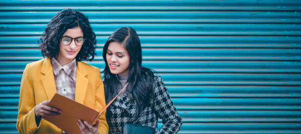 Young adult businesswomen discuss project together on the go. stock photo