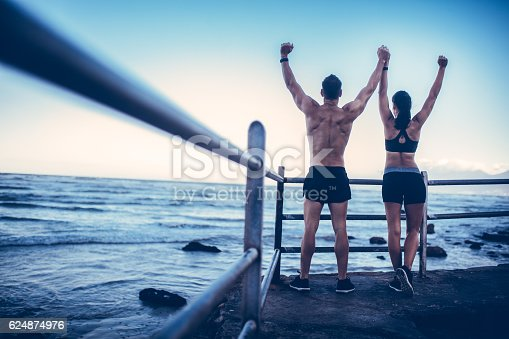 istock Young adult caucasian couple doing conquer pose after run 624874976
