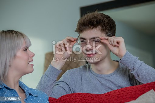 Young adult Caucasian man tries on eyeglasses at home with girlfriend