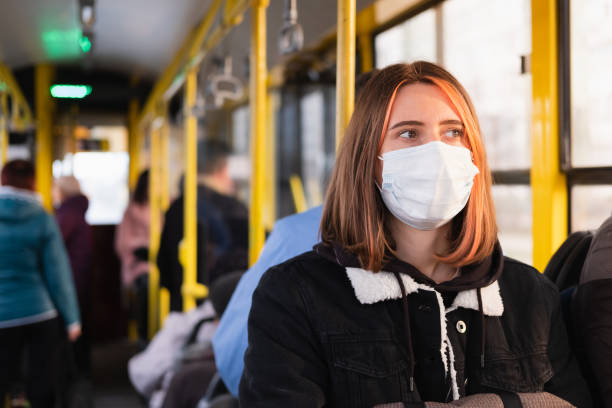 Young adult commutes in a protective face mask. stock photo