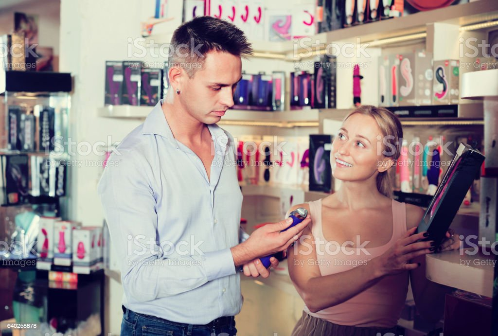 Young adult couple buying sex toys in shop stock photo