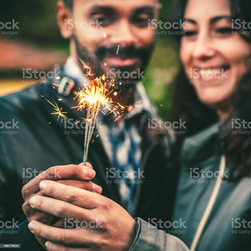 Young Adult Couple Celebrating with Sparklers Outdoors stock photo