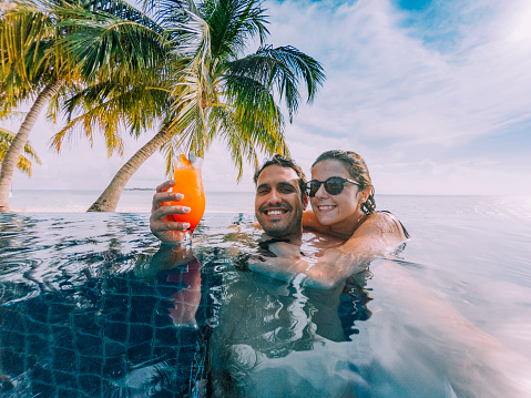 Young adult couple doing a selfie in the swimming pool in a paradisiac island