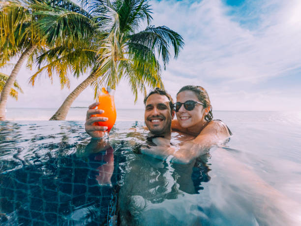 Young adult couple doing a selfie in the swimming pool in a paradisiac island stock photo