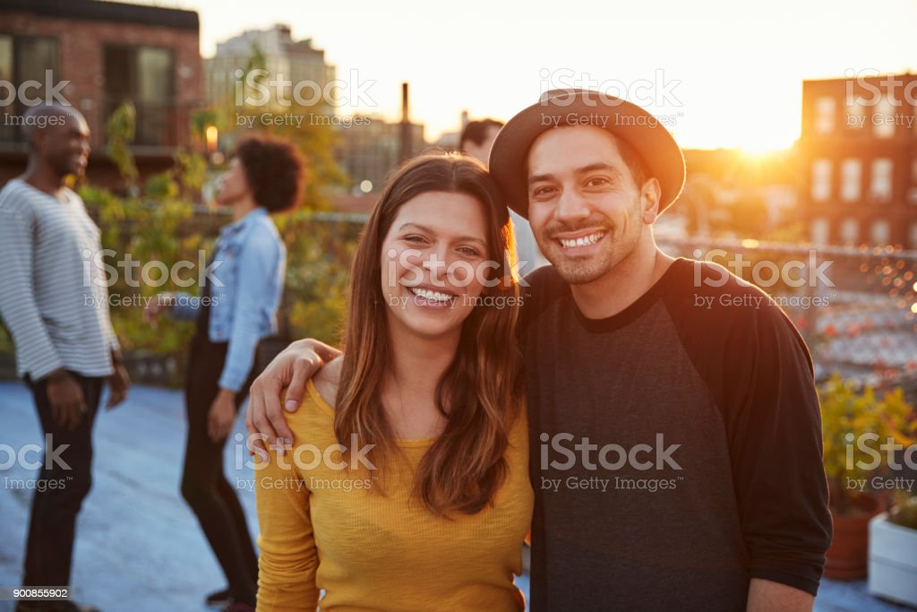 Young adult couple embracing at a rooftop party stock photo