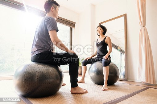 916126642istockphoto Young adult couple exercising together in a Gym 695600338