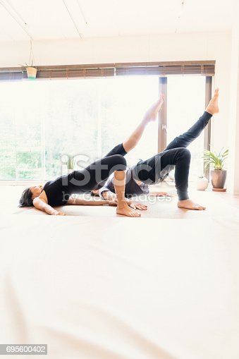 916126642istockphoto Young adult couple exercising together in a Gym 695600402