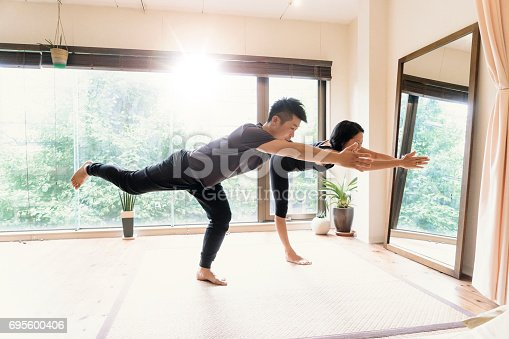 916126642istockphoto Young adult couple exercising together in a Gym 695600406
