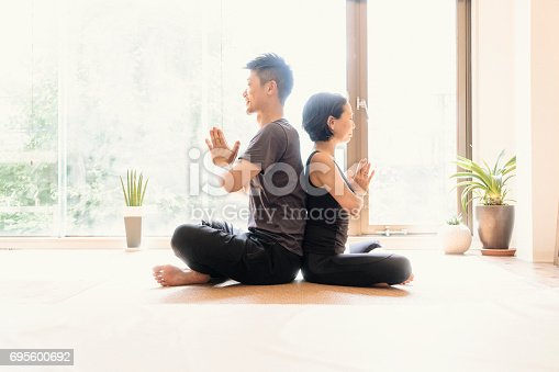 916126642istockphoto Young adult couple exercising together in a Gym 695600692