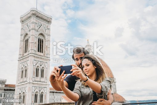 Young adult couple having a selfie during their vacation in Florence, Italy