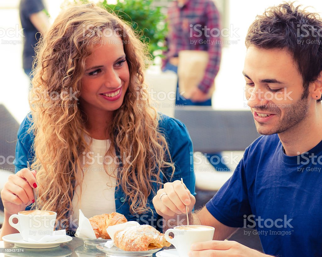 Young adult couple having breakfast outside a bar in Italy royalty-free stock photo