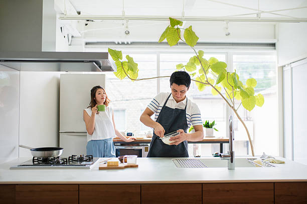 Young adult couple in the kitchen together stock photo