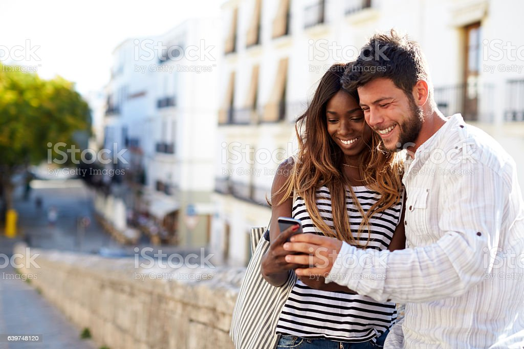 Young adult couple looking at smartphone, Ibiza, Spain stock photo