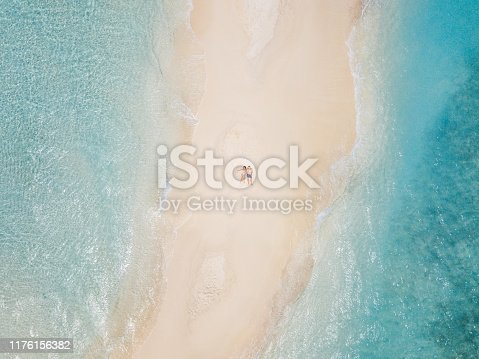 Young adult couple lying together on a sandbank against turquoise water in Maldives