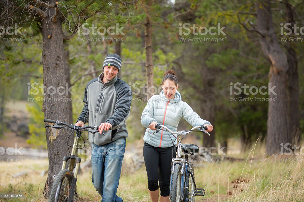 Young adult couple riding bikes outdoors in nature stock photo