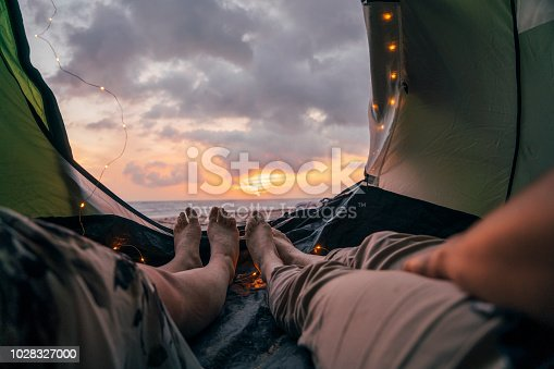 istock Young adult couple sleeping in a tent on the beach 1028327000