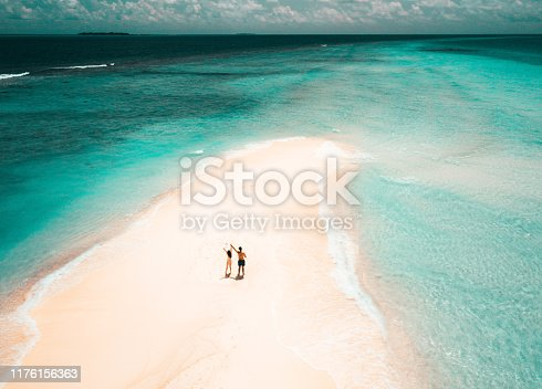 Young adult couple standing on a sandbank against turquoise water in Maldives