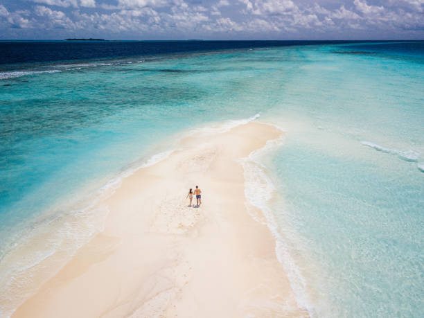 Young adult couple standing on a sandbank against turquoise water in Maldives stock photo