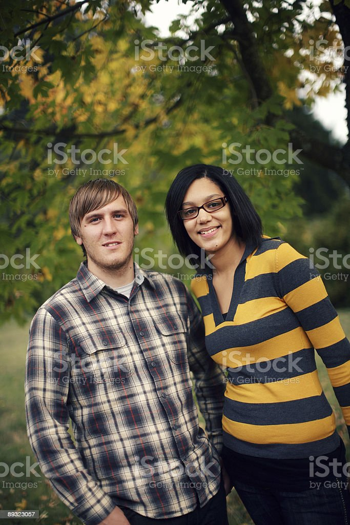 Young Adult Couple Standing Together under Fall Trees royalty-free stock photo