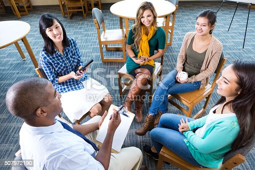 956725740istockphoto Young adult creative professionals discuss project in group 507972190