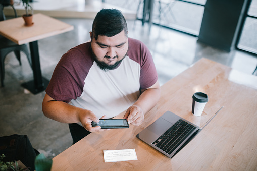 A Hispanic man in his 20's works on his computer in a public cafe, enjoying a latte in a paper cup.  He takes a photo of a paycheck with his smartphone for mobile deposit to his bank checking account.