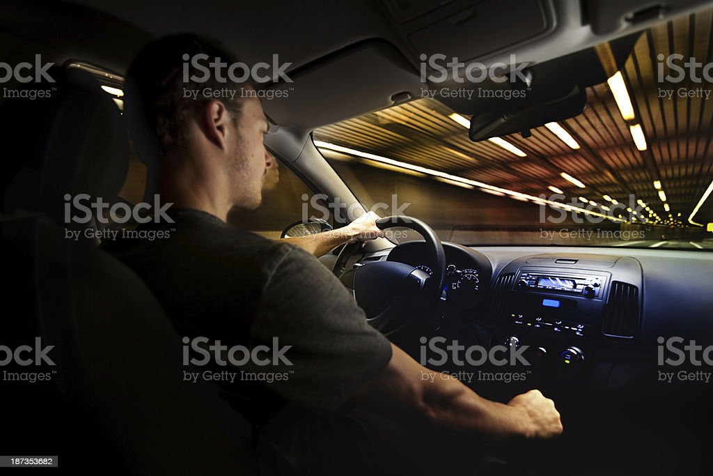 Young Adult Driving Over the Speed Limit in a Tunnel. stock photo