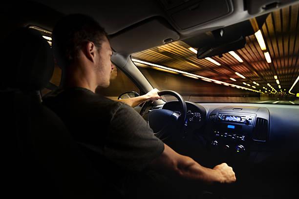jeune adulte en plus de la limitation de vitesse dans un tunnel. - voiture nuit photos et images de collection