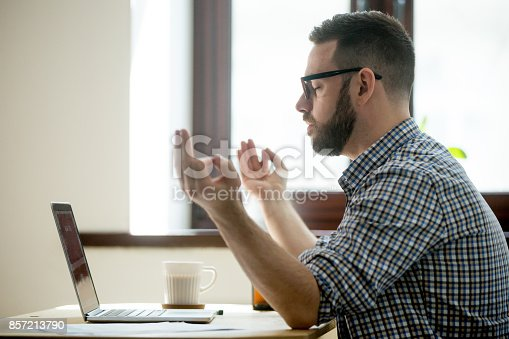 istock Young adult employee meditating in his office chair. 857213790
