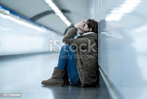 Young adult felling shame depressed and hopeless sitting alone on subway city ground in Depression Loneliness Mental health Emotional pain Social violence Abusive relationship and Harassment concept.