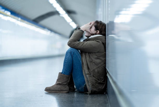 young adult felling shame depressed and hopeless sitting alone on subway city ground in depression loneliness mental health emotional pain social violence abusive relationship and harassment concept. - victim stock pictures, royalty-free photos & images