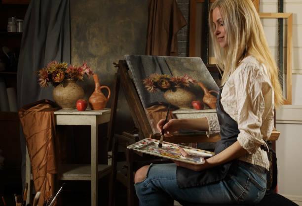 Joven artista adulta pinta una pintura al óleo - foto de stock