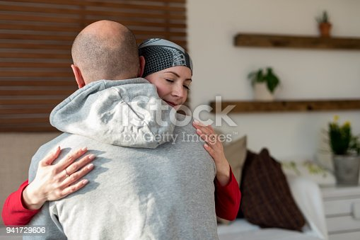 469949126 istock photo Young adult female cancer patient hugging her husband at home after treatment in hospital. Cancer and family support concept. 941729606