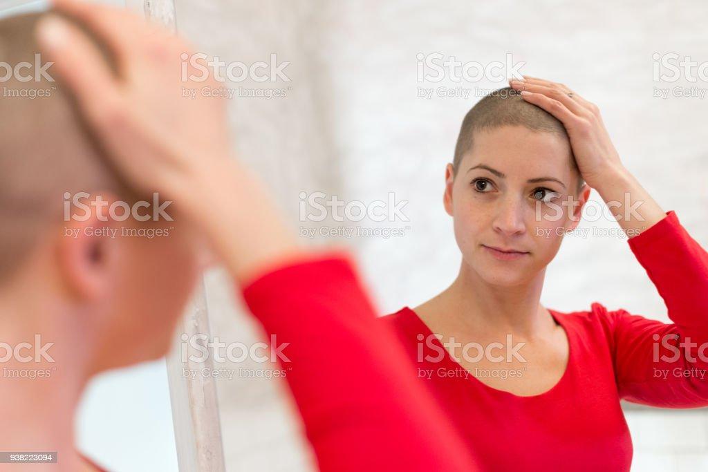Junge Erwachsene weibliche Krebspatienten Blick in den Spiegel, streichelte ihr neues kurzes Haar. – Foto