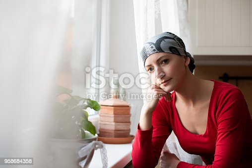Young adult female cancer patient wearing headscarf sitting by the window in the kitchen looking at camera.