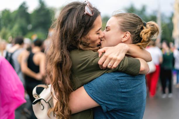 jong volwassen vrouwelijke koppel op pride parade - lesbische stockfoto's en -beelden