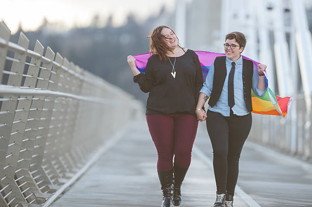 a young adult female couple is out on a walk together - transsexual stock photos and pictures