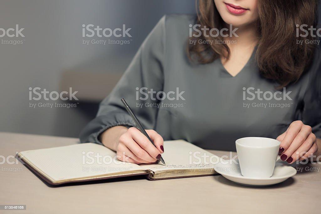 Junge Frauen mit Kaffeepause und Schreiben von Notizen - Lizenzfrei Aktenordner Stock-Foto