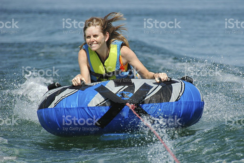 Young Adult Female Inner Tubing Behind Speedboat stock photo