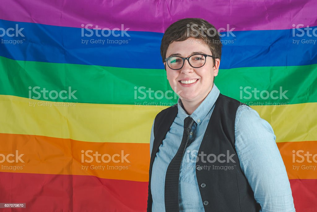 A young adult female is standing in front of a pride stock photo