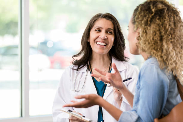 Young adult female patient talks to caring female doctor stock photo