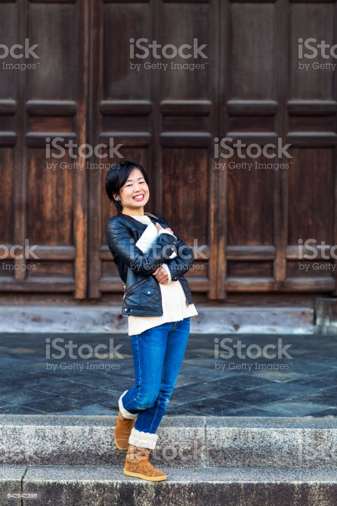 Young adult female stood holding a digital tablet and smiling to the camera. stock photo