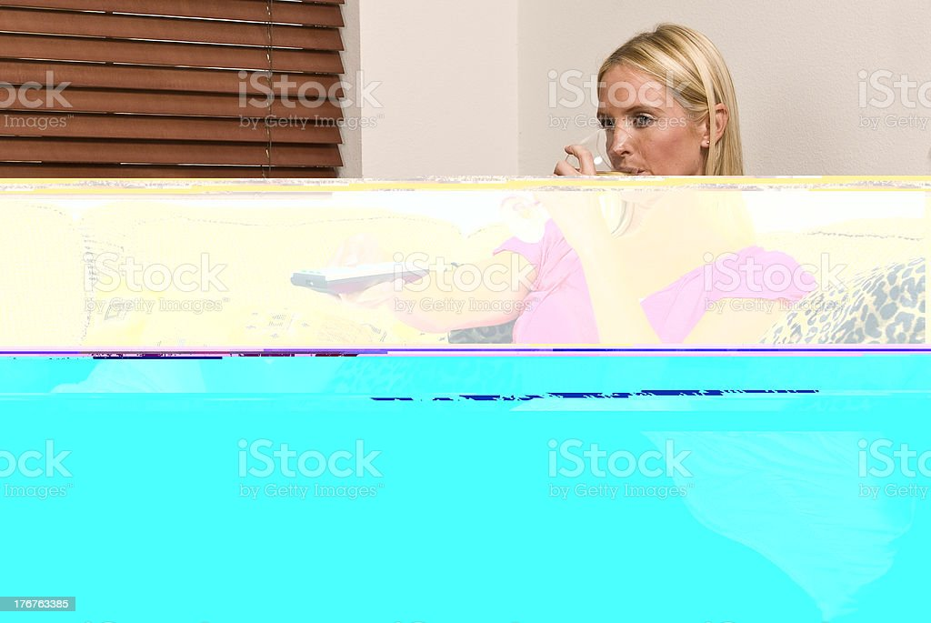 Young adult female watching television and enjoying glass of wine stock photo