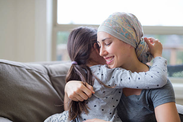 Young adult female with cancer hugging her daughter stock photo