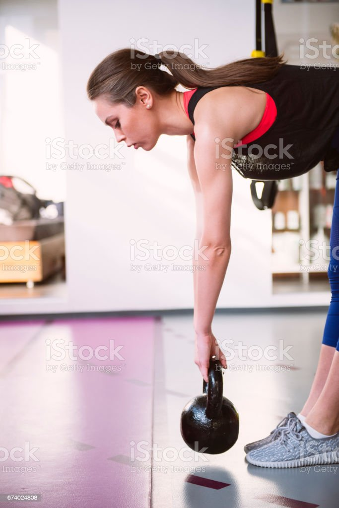 Young adult fitness woman doing swing exercise with a kettlebell royalty-free stock photo